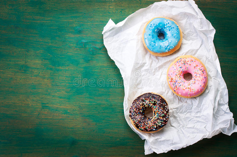Fresh sweet colorful homemade donuts on a green wooden vintage background for birthday or party. Top view, with free space for text royalty free stock photo