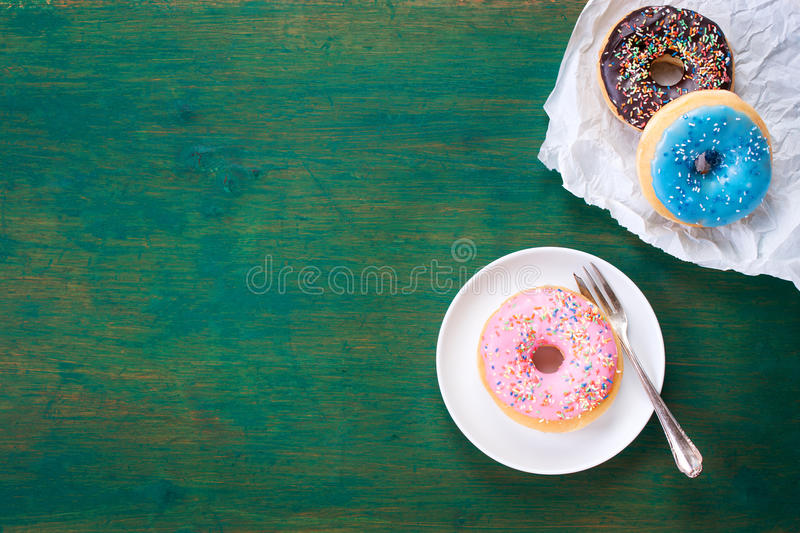Fresh sweet colorful homemade donuts on a green wooden vintage background for birthday or party. Top view, with free space for text royalty free stock photos