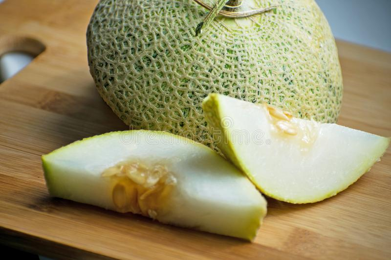 Fresh sweet green melon on the wooden board, tasty melons sliced on wooden board. Cantaloupe melon. Fresh sweet green melon on the wooden board. Cantaloupe stock photo