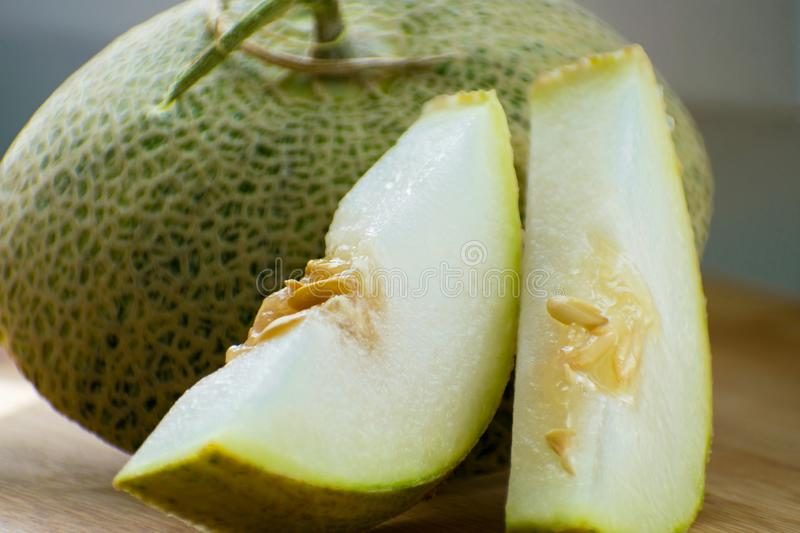 Fresh sweet green melon on the wooden board, tasty melons sliced on wooden board. Cantaloupe melon. Fresh sweet green melon on the wooden board. Cantaloupe stock photos