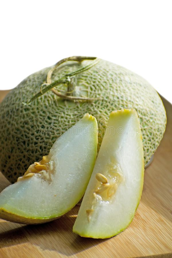 Fresh sweet green melon on the wooden board, tasty melons sliced on wooden board. Cantaloupe melon. stock image