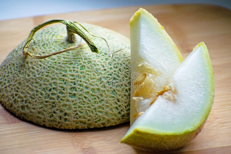 Fresh sweet green melon on the wooden board, tasty melons sliced on wooden board. Cantaloupe melon. Fresh sweet green melon on the wooden board. Cantaloupe royalty free stock photo