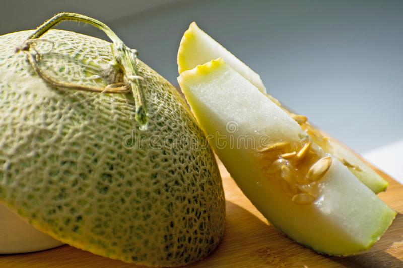 Fresh sweet green melon on the wooden board, tasty melons sliced on wooden board. Cantaloupe melon. Fresh sweet green melon on the wooden board. Cantaloupe stock photography