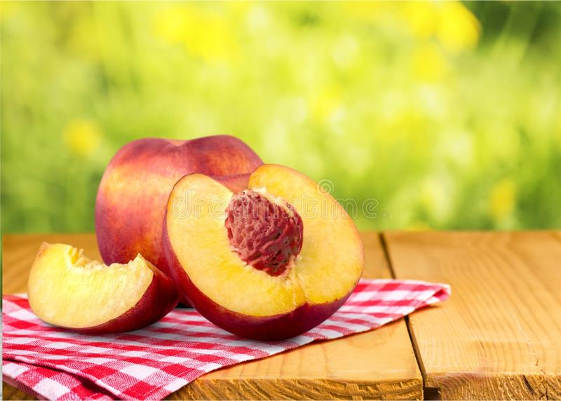 Fresh sweet peaches on a wooden background royalty free stock photo