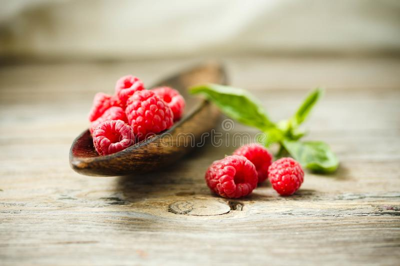 Fresh sweet raspberry and green basil in a wooden plate. Horizon royalty free stock photos