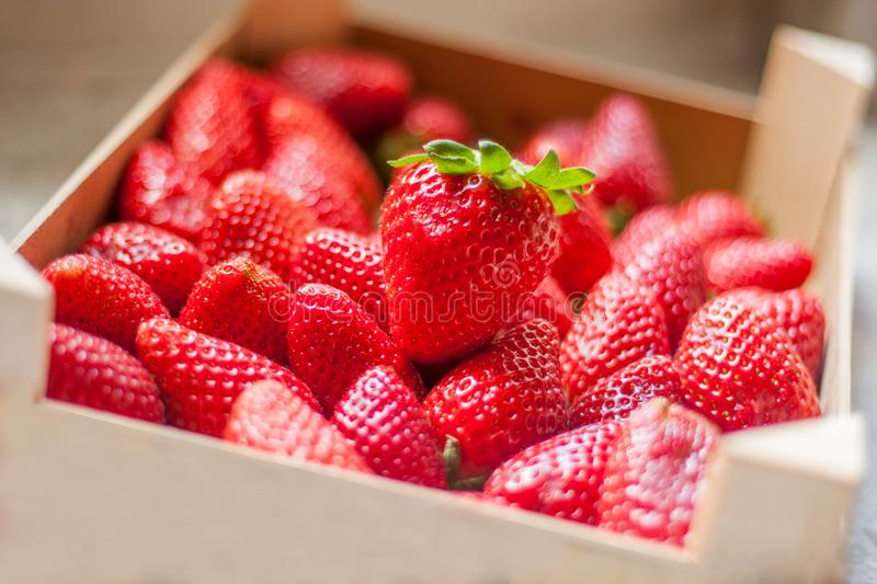 Fresh and sweet ripe red strawberries. From Spain on the kitchen counter. Stored in a natural wooden plastic free box or case stock photography