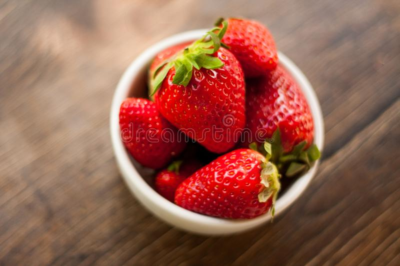 Fresh and sweet ripe red strawberries. From Spain on a dark wooden table outdoors. Served as a healthy snack or dessert in a small white ceramic bowl royalty free stock photo