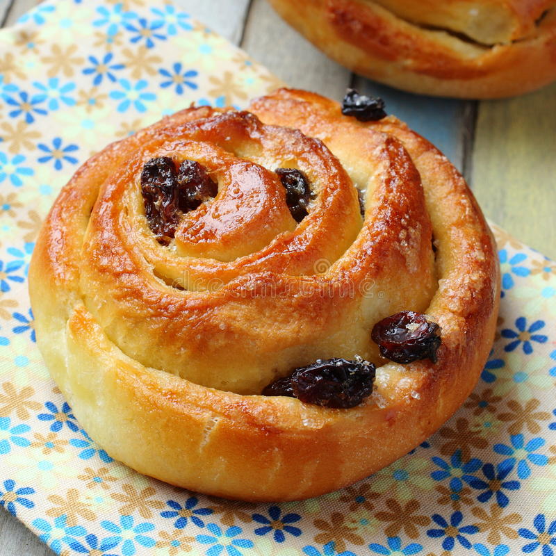 Fresh sweet swirl buns with raisins on colored wooden table stock photos