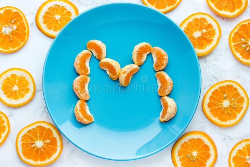 Fresh tangerine mandarin slices on blue plate royalty free stock photo