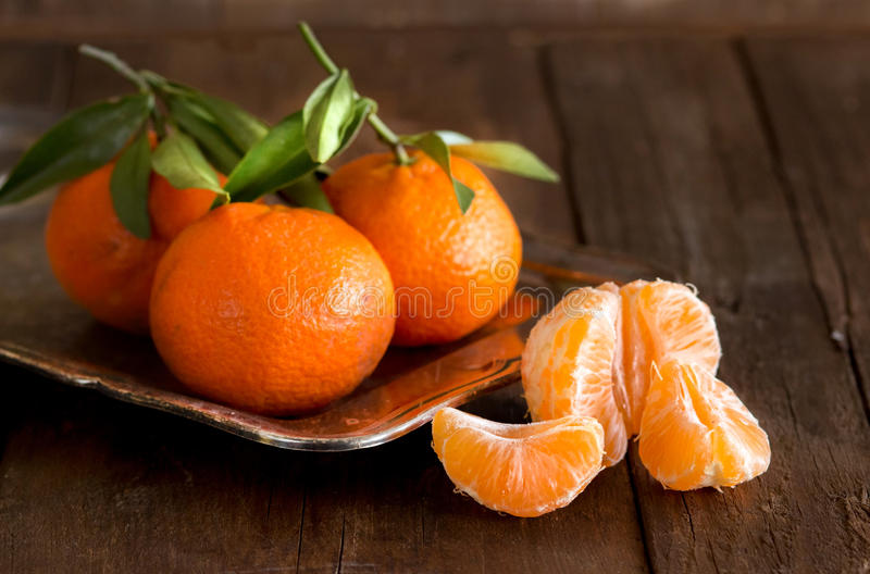Fresh Tangerines. With green leaves on a wooden background royalty free stock image