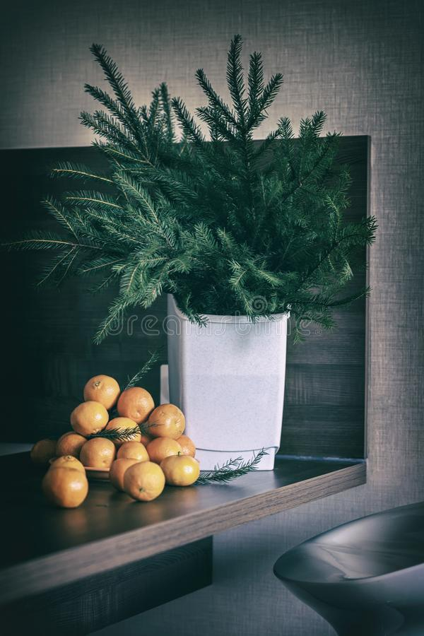 Fresh tangerines on a wooden table with coniferous branches of spruce. Christmas composition, winter holiday. Vintage royalty free stock photography