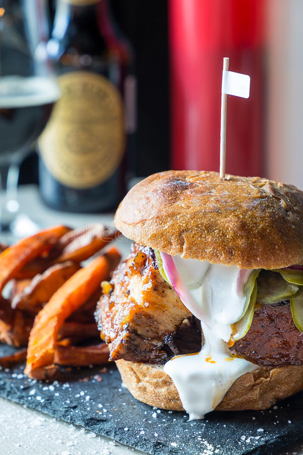 Fresh Tasty Bacon Big Burger with Fried Sweet Potatoes and White Sauce and Soft Drinks. Close-up, Vertical View stock photo