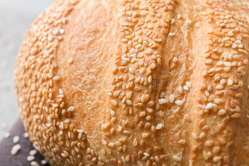 Fresh tasty bread with sesame seeds on table, closeup royalty free stock photos