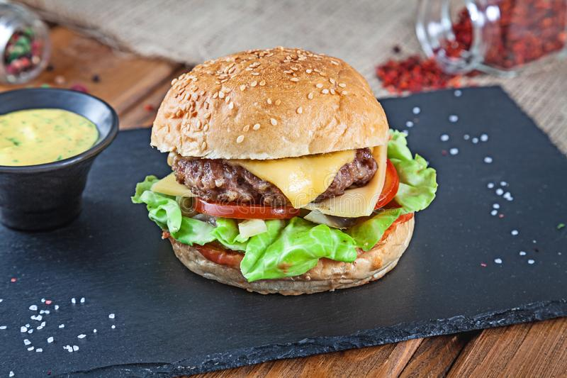 Fresh tasty burger with cheese, lettuce, tomato, cucumber on black stone with sauce. American fast food. Cheeseburger with copy stock photo