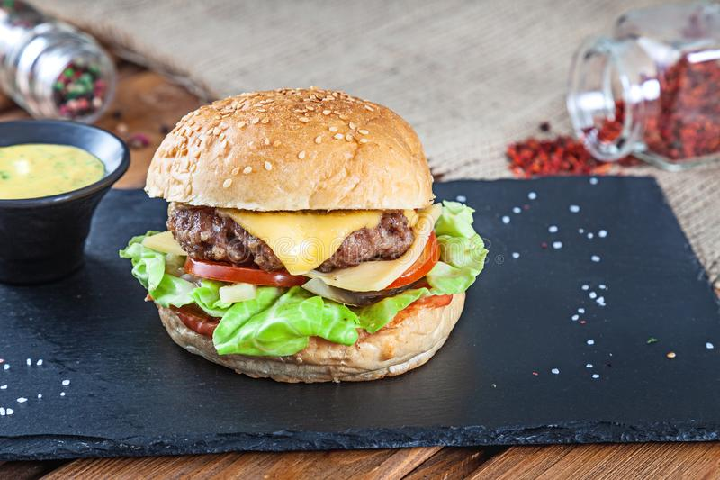 Fresh tasty burger with cheese, lettuce, tomato, cucumber on black stone with sauce. American fast food. Cheeseburger with copy stock photography
