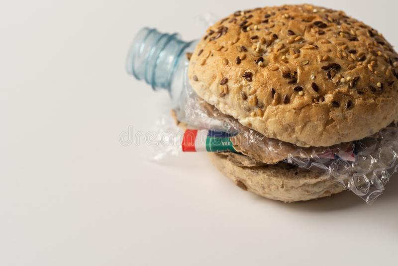 Fresh tasty burger with plastic waste and paper cardboard inside on white background. Recycled waste in our food concept.  royalty free stock images