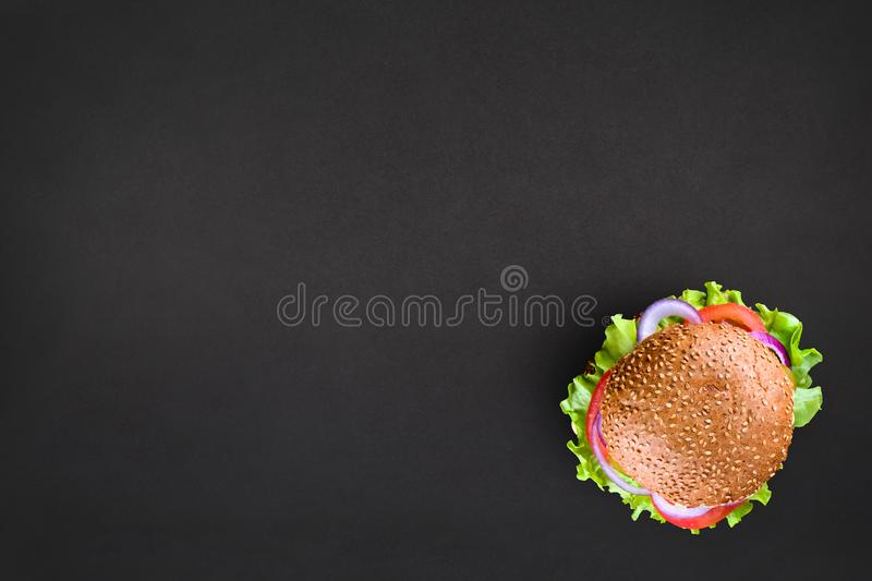 Fresh tasty burger Top view on black background. Tasty and appetizing cheeseburger. Vegetarian burger with place for royalty free stock photo