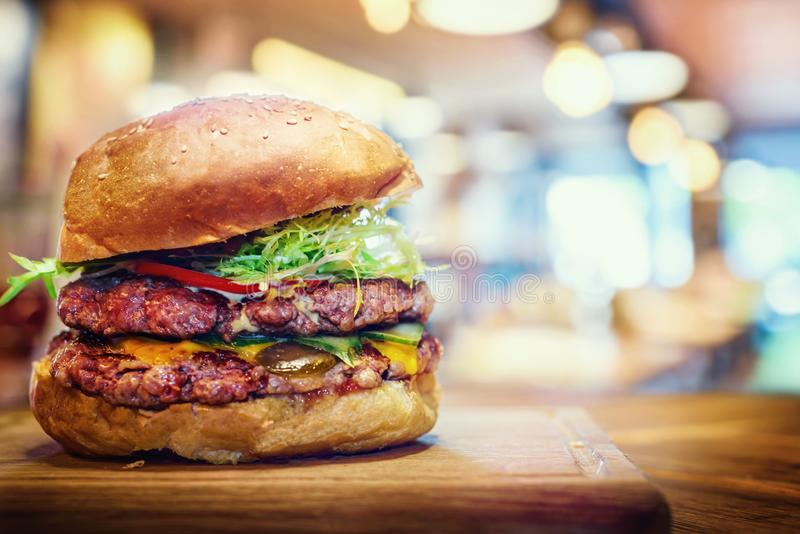 Fresh tasty burger on wooden table. Hamburger fast food restaurants background. royalty free stock photography