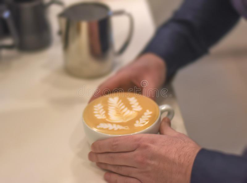 Fresh tasty cafe latte with latte art in barist hands in cafeteria. Close royalty free stock image