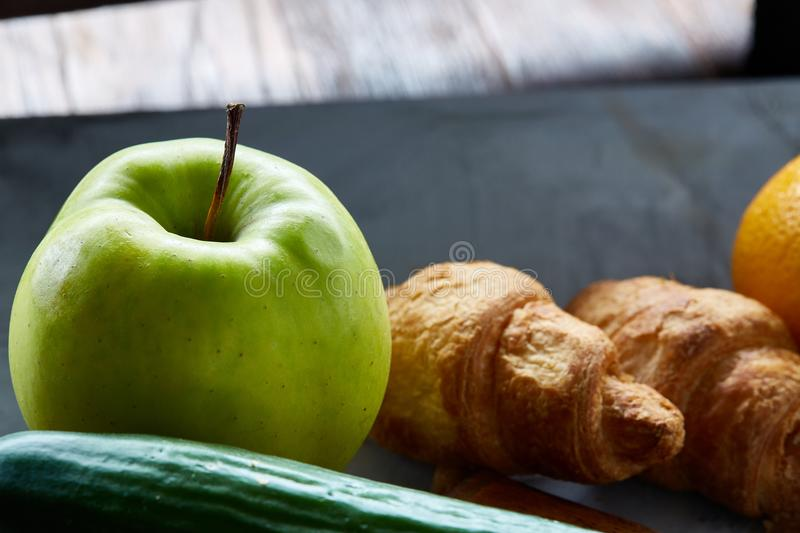 Fresh tasty croissants with apple on dark cutting board, close-up, selective focus royalty free stock photos
