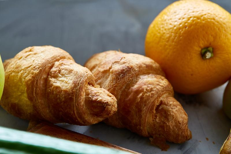 Fresh tasty croissants with apple on dark cutting board, close-up, selective focus royalty free stock photo