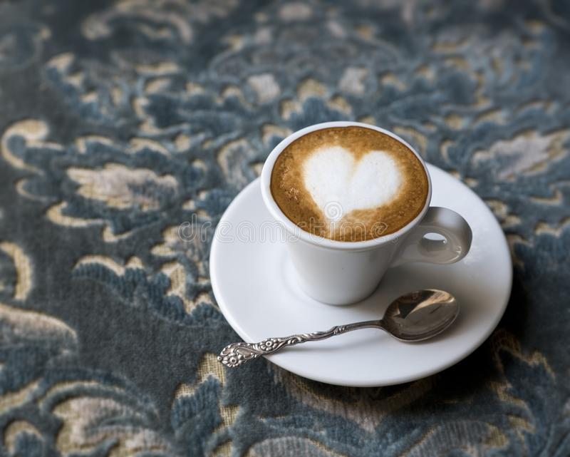 Fresh tasty espresso cup of hot coffee with coffee beans on a blue antique background. Drawing on coffee - heart. Copy space royalty free stock photography
