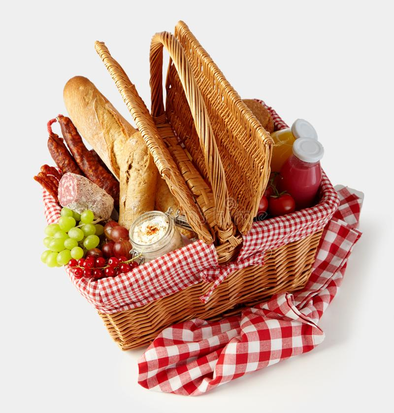 Fresh tasty food in a wicker picnic basket. Isolated on white with fruit, juice, spicy sausages and crusty bread viewed high angle royalty free stock photos