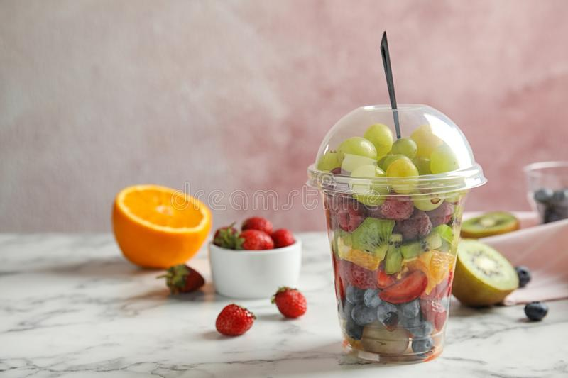 Fresh tasty fruit salad in plastic cup on white marble table. Space for text stock image