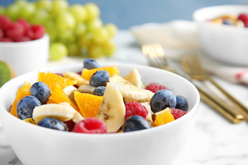 Fresh tasty fruit salad on white marble table. Closeup royalty free stock photo