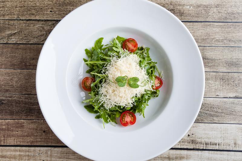 Rucola salad. Fresh tasty healthy rucola salad in white plate stock photo