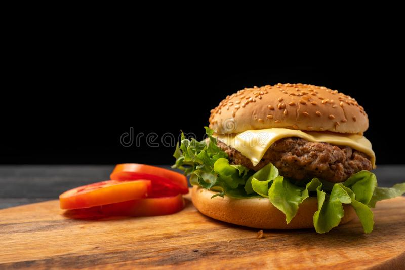 Fresh tasty homemade hamburger with fresh vegetables, lettuce, tomato, cheese beside sliced tomatoes on a cutting board. Free spac. E for text royalty free stock images