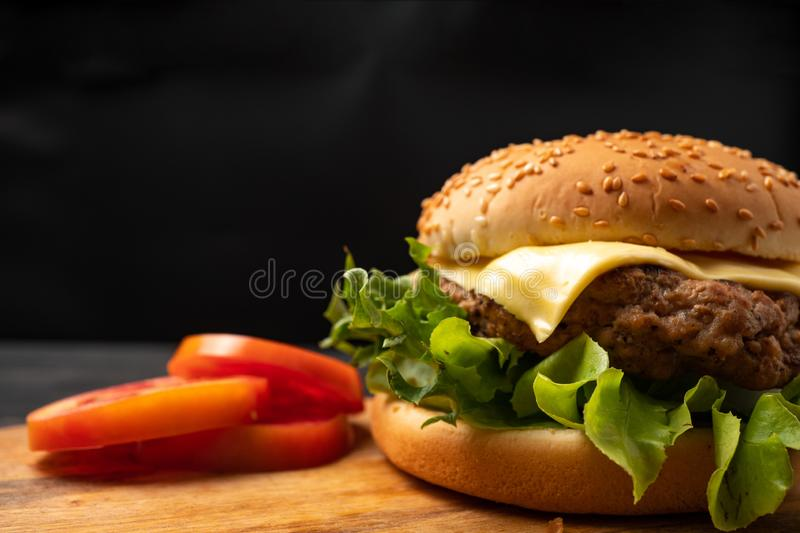 Fresh tasty homemade hamburger with fresh vegetables, lettuce, tomato, cheese beside sliced tomatoes on a cutting board. Free spac. E for text stock photos