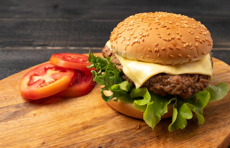 Fresh tasty homemade hamburger with fresh vegetables, lettuce, tomato, cheese beside sliced tomatoes on a cutting board. Free spac. E for text stock images