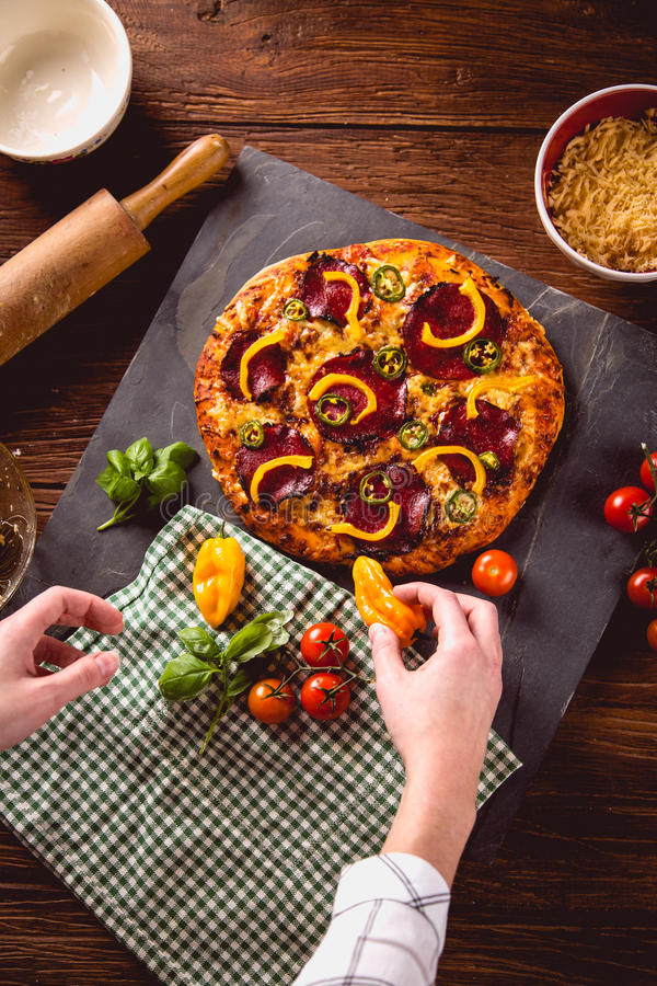 Fresh and tasty homemade pizza on wooden table with ingredients.  stock images