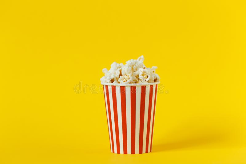 Fresh tasty popcorn and red cup on color yellow background, side view with space for text. Cinema snack royalty free stock photo