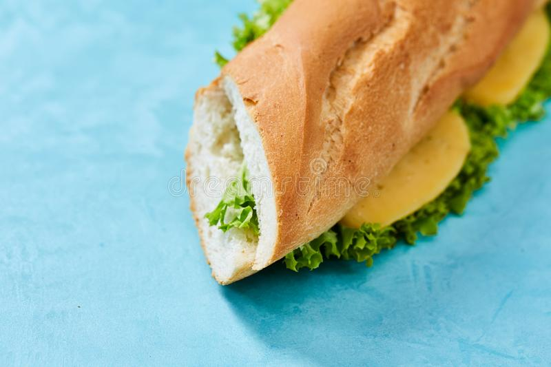 Fresh and tasty sandwich with cheese and vegetables on cutting board over blue background, selective focus. stock photography