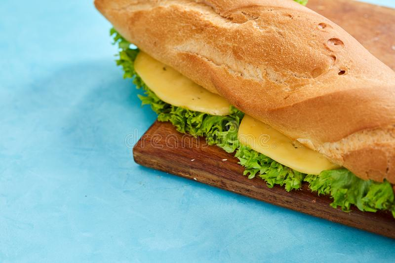 Fresh and tasty sandwich with cheese and vegetables on cutting board over blue background, selective focus. royalty free stock image