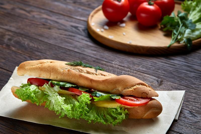 Fresh and tasty sandwich with cheese and vegetables on paper napkin over wooden background, selective focus, top view stock photo