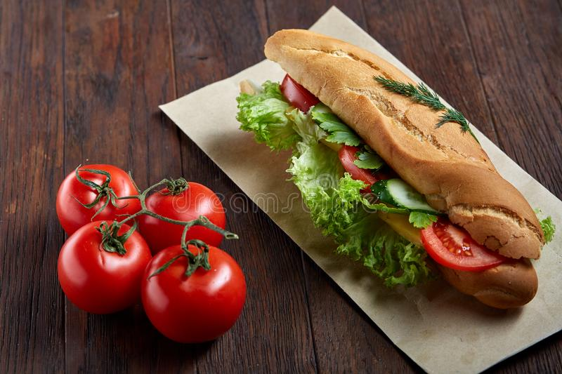 Fresh and tasty sandwich with cheese and vegetables on paper napkin over wooden background, selective focus, top view stock images