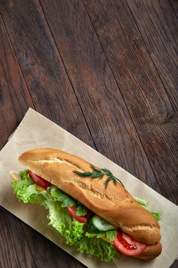 Fresh and tasty sandwich with cheese and vegetables on paper plate over wooden background, selective focus, top view royalty free stock images