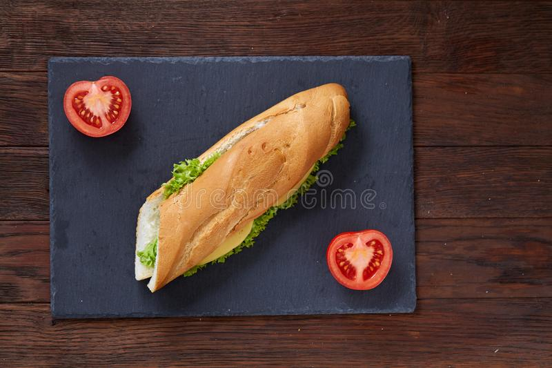 Fresh and tasty sandwich with cheese and vegetables on cutting board over white textured background, selective focus. royalty free stock images