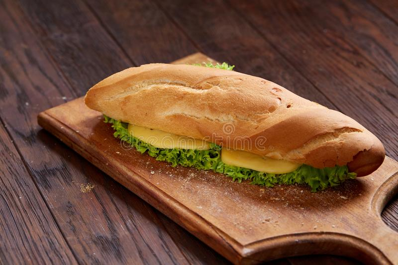 Fresh and tasty sandwich with cheese and vegetables on cutting board over white textured background, selective focus. stock image