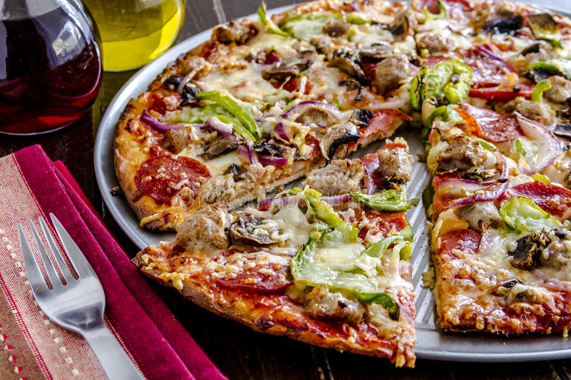 Fresh Thin Crust Supreme Pizza. Close up of fresh baked thin crust supreme pizza surrounded by containers of red wine vinegar and olive oil with striped napkin stock photography
