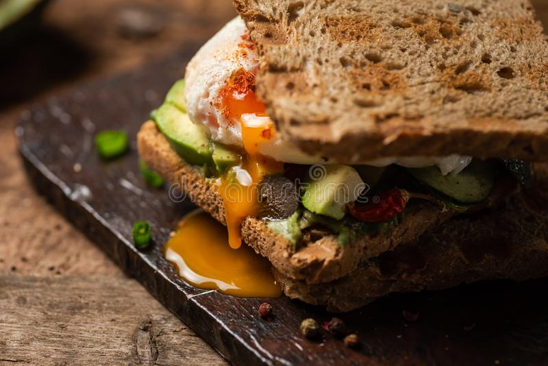 Toast sandwich with fried egg. Fresh toast sandwich with fried egg and avocado, guacamole, toasted, runny, sunny, side, up, close, served, plate, food, snack royalty free stock photos