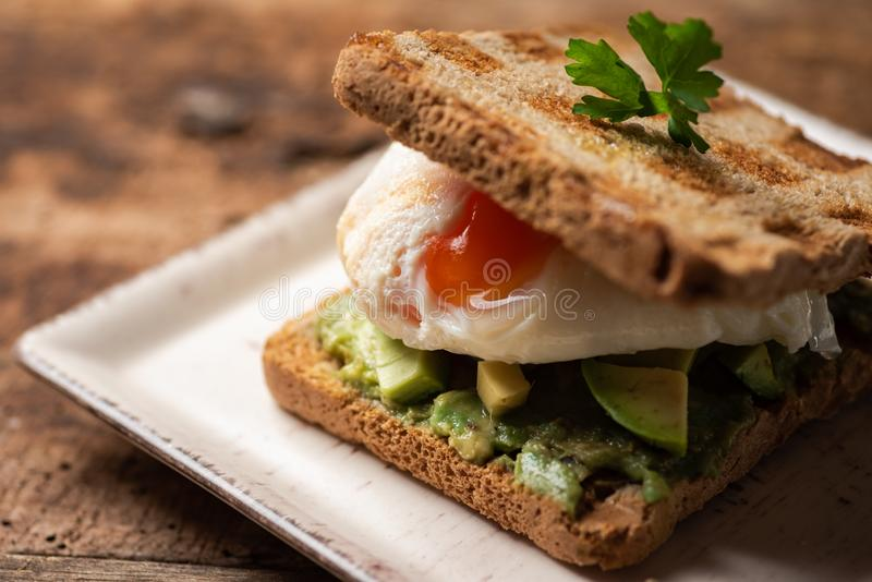 Toast sandwich with fried egg. Fresh toast sandwich with fried egg and avocado, guacamole, toasted, sunny, side, up, close, served, plate, food, snack, bread stock photography