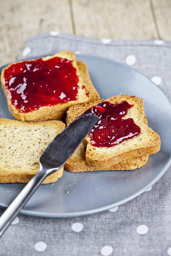 Fresh toasted cereal bread slices with homemade cherry jam and knife on grey plate closeup on grey linen napkin background stock photography