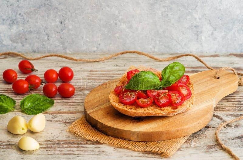Fresh tomato bruschetta with basil and garlic on rustic background. Fresh tomato bruschetta with basil, onion on rustic background royalty free stock photos