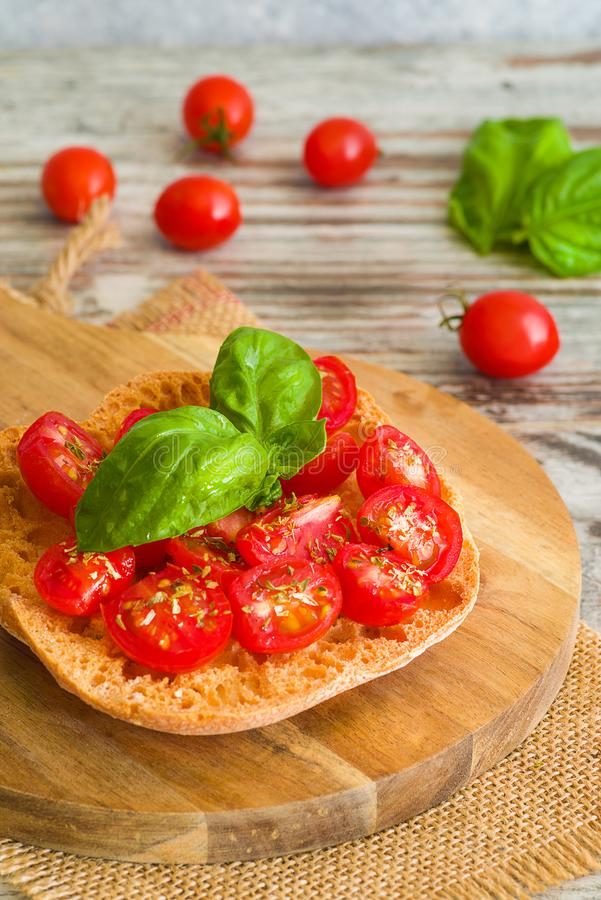 Fresh tomato bruschetta with basil on wooden background. Fresh tomato bruschetta on wooden background. Italian food appetizer with fresh basil royalty free stock photo