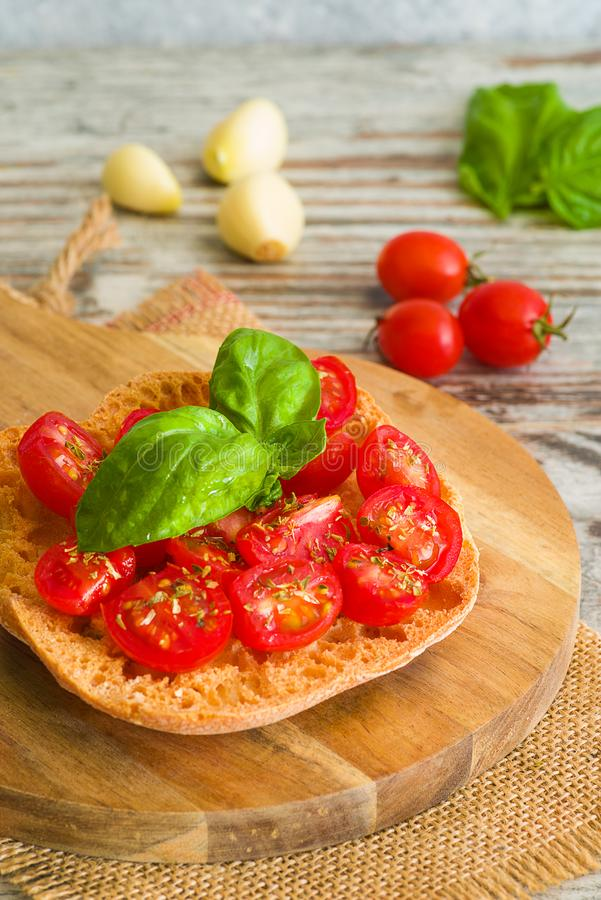 Fresh tomato bruschetta with basil on wooden background. Fresh tomato bruschetta on wooden background. Italian food appetizer with fresh basil and garlic royalty free stock photo