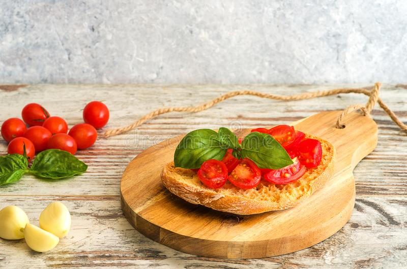 Fresh tomato bruschetta on wooden background, with basil and gar. Fresh tomato bruschetta on wooden background. Italian food appetizer with fresh basil, and royalty free stock photo